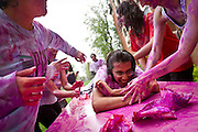 Raghav Malik '13 reacts to being covered in colors during the Holi Festival of Colors at Grinnell College on Saturday. The holiday is noted for participants throwing powdered colors and water at each other and serves to mark the beginning of the spring season.<br /> BEN BREWER/Grinnell College