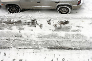 view from above of a parked car in the snow with just plowed street