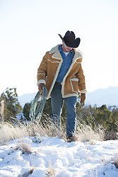 cowboy outdoors walking with a lasso