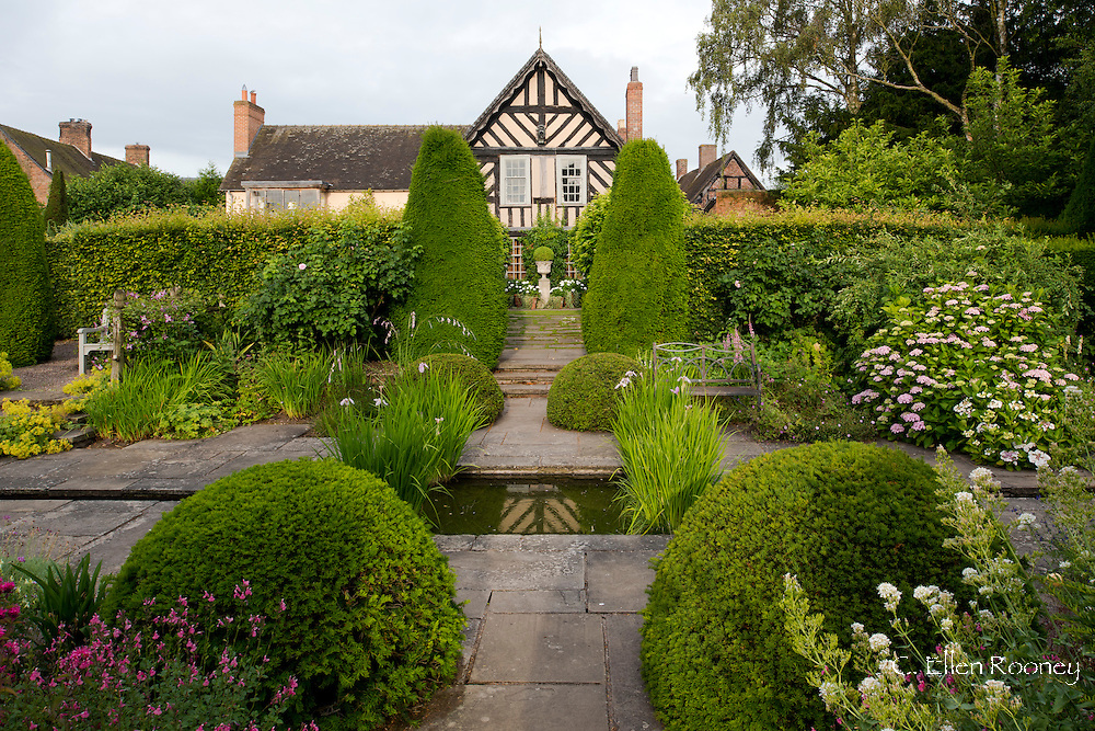 A view over The Rill Garden and Buxus sempervirens to The Old Garden and the house at Wollerton Old Hall, Wollerton, Market Drayton, Shropshire, UK