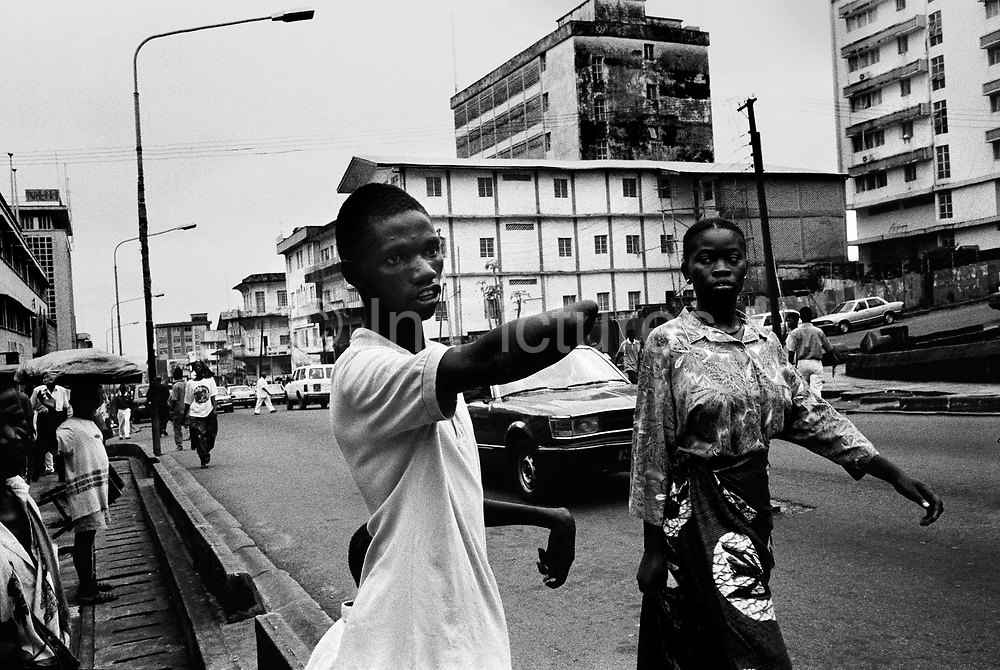Hassan Fofona begs for money outside the central post office in Freetown. Hassan, 16, crippled by polio since he was 10 was caught by the rebels who hacked of his good arm on a tree stump. From a very poor family, he cannot work and so must beg.  freetown, Sierra Leone 1999