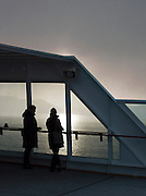 Passengers aboard a cruise ship watch sunset in the early, winter afternoon in Finnmark region of northern Norway
