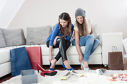 Two young female friends sitting side by side on couch at home trying on high heels