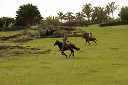 Chile, Easter Island: Horse riders galloping at Ahu Tahai near Hanga Roa..Photo #: ch235-33126..Photo copyright Lee Foster www.fostertravel.com lee@fostertravel.com 510-549-2202