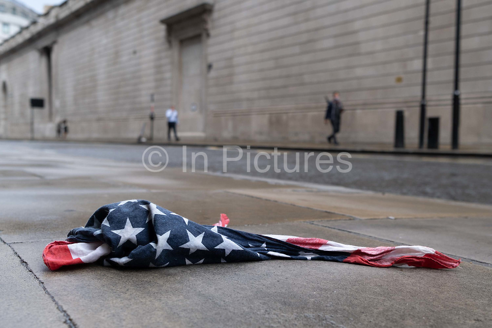 After a rain shower, an American Stars and Stripes flag bandana lies on the wet pavement opposite the high wouter wall of the Bank of England in the City of London, the UK capitals financial district, on 17th August 2020, in the City of London, England.