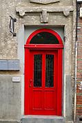 red door in a dilapidated building deterioration, Bucharest Romania