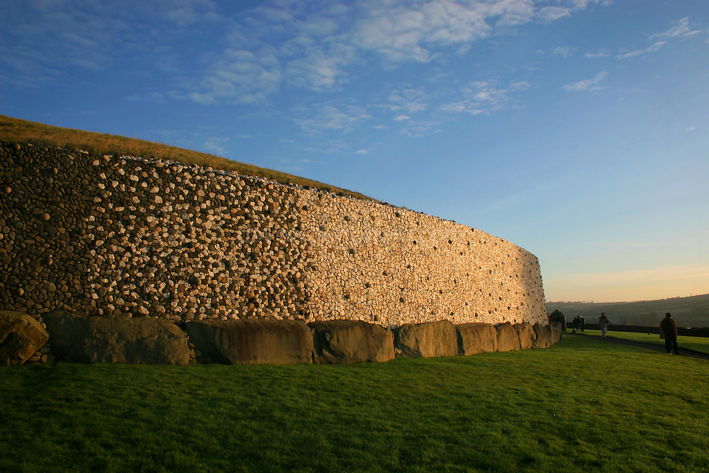 Solstice sunlight hitting the outside of Newgrange, which is arranged a giant annual clock, marking out the shortest day of the year. ....This quartz and granite face is a modern reconstruction - using the original materials - of how Newgrange must have looked 5,000 years ago. The quartz came from about 60km south, while the granite rocks came from farther north. The stones on the bottom weigh between 1 and 10 tonnes - and were put here 5,000 years ago!........