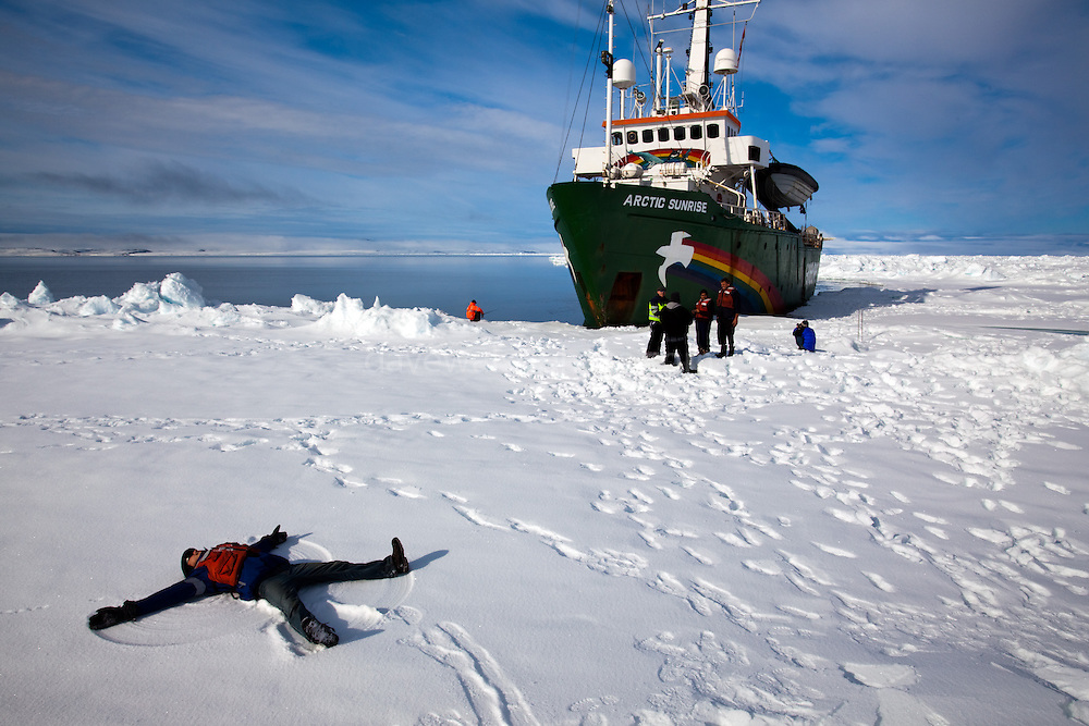 Texas making a snow angel on the sea ice, Lincoln Sea, Arctic Ocean, in front of the Arctic Sunrise