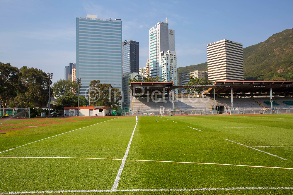Aberdeen Sports Ground being overlooked by high-rise buildings on Wong Chuk Hang Road, Hong Kong. The buildings include from left to right: One Island South, L'Hotel, and the Gee Chang Hong centre.