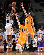 Kansas State forward hits a three pointer over pressure from Vermont defenders Martin  Klimes (20) and Joe Trapani (14), during first half action at Bramlage Coliseum in Manhattan, Kansas, March 14, 2007. Cartier Martin lead all scores with 19 points as  K-State beat Vermont in the first round of the NIT 59-57.