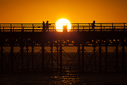 © Licensed to London News Pictures. 27/12/2017. Southsea, UK.  People making the most of the last light as the sun sets over Southsea pier this afternoon. Clearing skies will cause the temperatures drop overnight. Photo credit: Rob Arnold/LNP