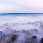 Waves overtake rocks at sunset on the ocean. Image made in the Bahamas.