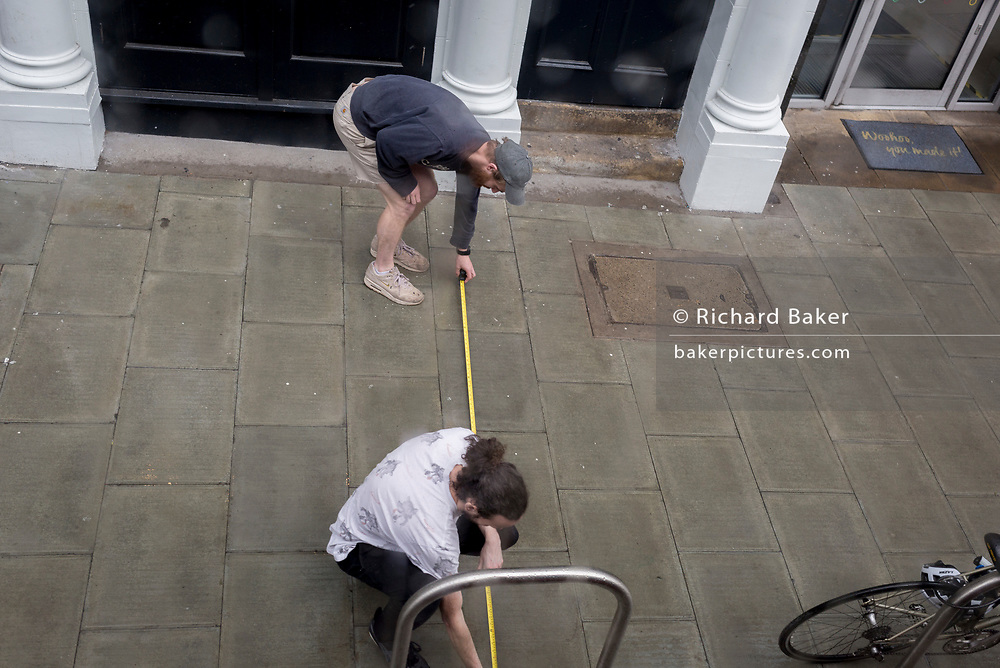 Two men take measurements by stretching a measuring tape across the pavement in Waterloo SE1, on 9th May 2019, in London, England.