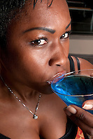 Young woman african american drinking a blue martini cocktail in a restaurant.