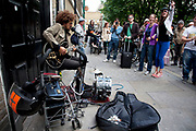 Busker Lewis Floyd Henry playing his music on Brick Lane in the East End of London. He is a well known and quite brilliant performing his blues based busking music.