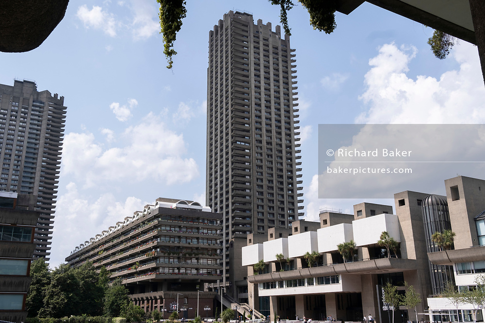 An exterior summer landscape of the Shakespeare Tower at the Barbican, on 21st July 2021, in London, England. The Barbican Centre is a performing arts centre in the Barbican Estate of the City of London but whose area was formerly known as Cripplegate - destroyed on the evening of 29 December 1940, when tens of thousands of bombs and incendiaries were dropped on the City by the German Luftwaffe in WW2.