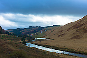 River runs along a valley in the Brecon Beacons mountain range in Wales, UK