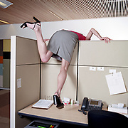 Businesswoman leaning over office cubicle wall