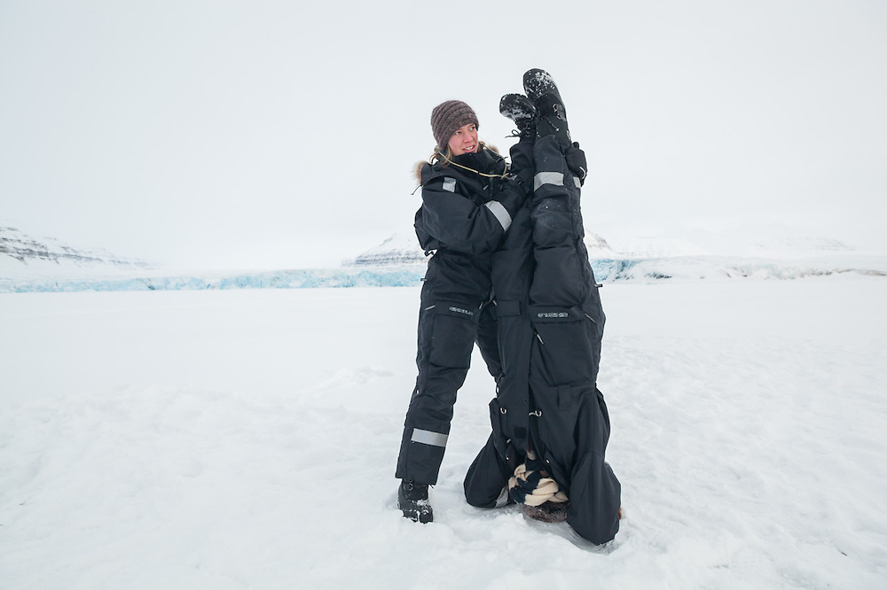UNIS student Sofie Vej Ugelvig helps her classmate Þorbjörg Sigfúsdóttir do a hand stand on the sea ice in Templefjorden at the terminus of Tunabreen, Svalbard.