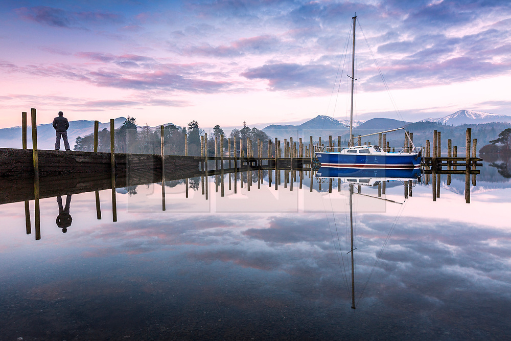 © Licensed to London News Pictures. 06/03/2020. KeswickUK. A boat & its jetty reflect into the calm water of Derwentwater lake at dawn this morning in Cumbria. Photo credit: Andrew McCaren/LNP