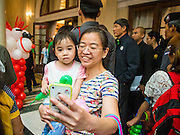 10 JANUARY 2015 - BANGKOK, THAILAND: People wait for Thai Prime Minister Gen. Prayuth Chan-ocha to come into an auditorium during Children's Day festivities at Government House in Bangkok. National Children's Day falls on the second Saturday of the year. Thai government agencies sponsor child friendly events and the military usually opens army bases to children, who come to play on tanks and artillery pieces. This year Thai Prime Minister General Prayuth Chan-ocha, hosted several events at Government House, the Prime Minister's office.    PHOTO BY JACK KURTZ