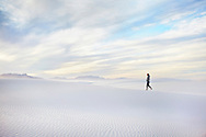 A woman walks up a sand dune during sunset at White Sands National Monument, New Mexico.