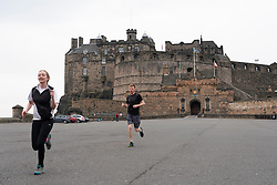 Edinburgh, Scotland, UK. 24 March, 2020.  Deserted streets in the heart of the Old Town tourist district in Edinburgh. All shops and restaurants are closed with very few people venturing outside following the Government imposed lockdown today. Pictured; Joggers on a morning run at the deserted Edinburgh Castle Esplanade. Iain Masterton/Alamy Live News