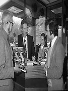 Derek Dougan's name goes in the book...1980-04-16.16th April 1980.16-04-1980.04-16-80..Photographed at Hodges Figgis, Stephen's Court, St Stephen's Green, Dublin:..Fromer Northern Irish soccer international and English League player Derek Dougan signing a copy of his book 'Doog' for customer Peter Moynihan, Sandyford, Co Dublin (right of picture)...Also in picture..Robert Twigg, manager of Hodges Figgis and cashier Norma Doyn (Tallaght, Dublin).....