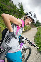 Mountainbiker with pain in back, Kampenwand, Bavaria, Germany