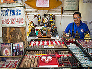 27 NOVEMBER 2015 - BANGKOK, THAILAND:  An amulet vendor on Maharat Road in Bangkok waits for customers. Hundreds of vendors sell amulet and Buddhist religious paraphernalia to people in the Amulet Market, a popular tourist attraction along Maharat Road north of the Grand Palace near Wat Maharat in Bangkok. Bangkok municipal officials announced that they are closing the market and forcing vendors to relocate to an area about one hour outside of Bangkok. The closing of the amulet market is the latest in a series of municipal efforts to close and evict street vendors and markets from areas that have potential for redevelopment. The street vendors will be evicted from the area by Sunday, Nov. 29.   PHOTO BY JACK KURTZ