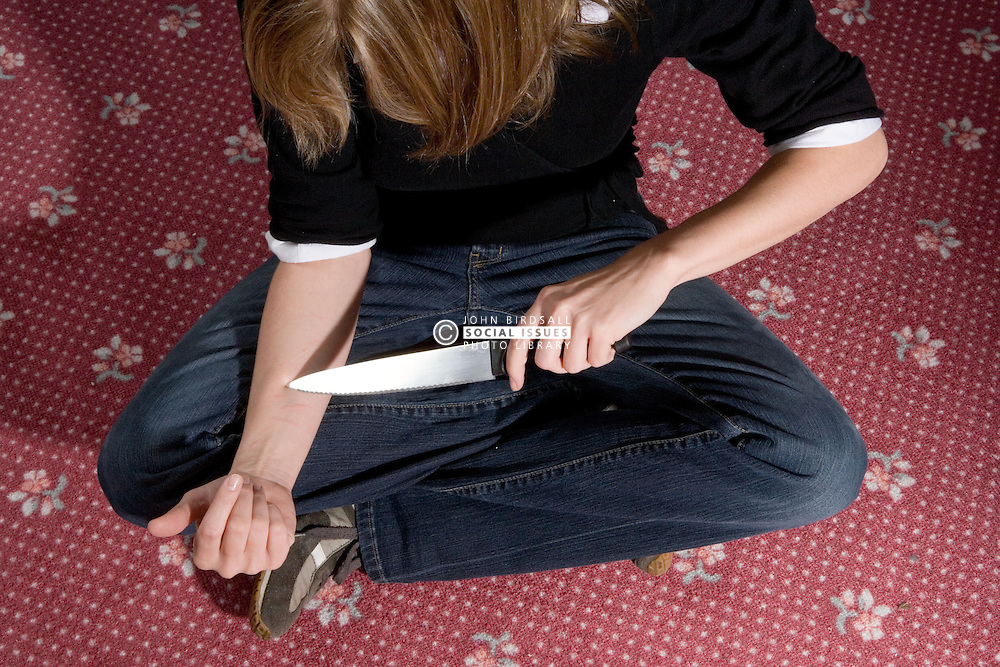 Young woman inflicting selfharm to her wrist,