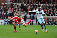 West Ham's Alou Diarra ® goes past Henri Lansbury of Nottingham Forest. FA Cup with Budweiser, 3rd round, Nottingham Forest v West Ham Utd match at the City Ground in Nottingham, England on Sunday 5th Jan 2014.<br /> pic by Andrew Orchard, Andrew Orchard sports photography.