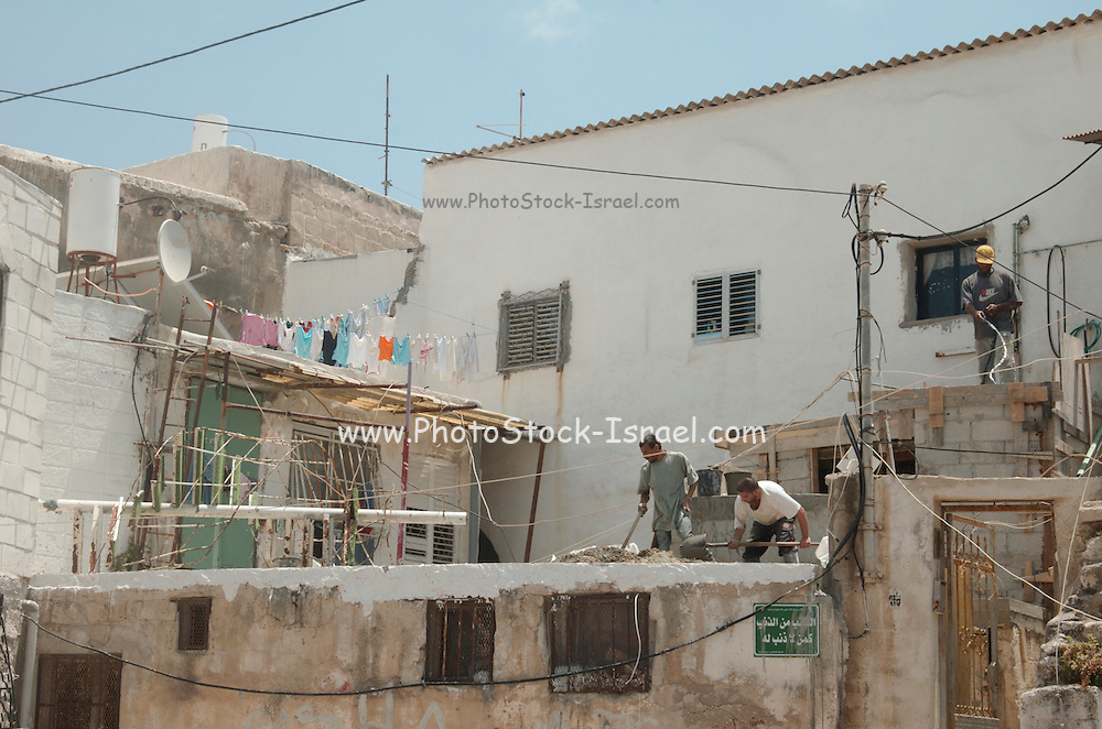 Israel, acre, dwellings and hovels in the old city, construction workers building a house
