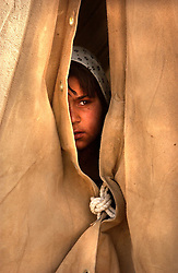ZHARE DASHT,AFGHANISTAN - SEPT. 3: An Afghan child who was living in a camp around Spin Boldak, near the border of Pakistan and southern Afghanistan, looks out of her new home after she was relocated to the desolate, dusty encamptment of Zhare Dasht by the UNHCR September 3, 2002.  As an estimated 1.6 million Afghan refugees return to Afghanistan,  ethnic Pashtuns from northern Afghanistan are seeking safety in refugee camps in the south. Numbering up to 120,000,  Pashtuns are fleeing the Tajik- and Uzbek-dominated cities of the north out of fear and prefer to live in the dismal camps like Zhare Dasht which is set in the middle of a desert about 30 kilometers west of Kandahar. (Photo by Ami Vitale/Getty Images)