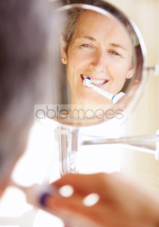 Woman Looking into Round Mirror Brushing Teeth