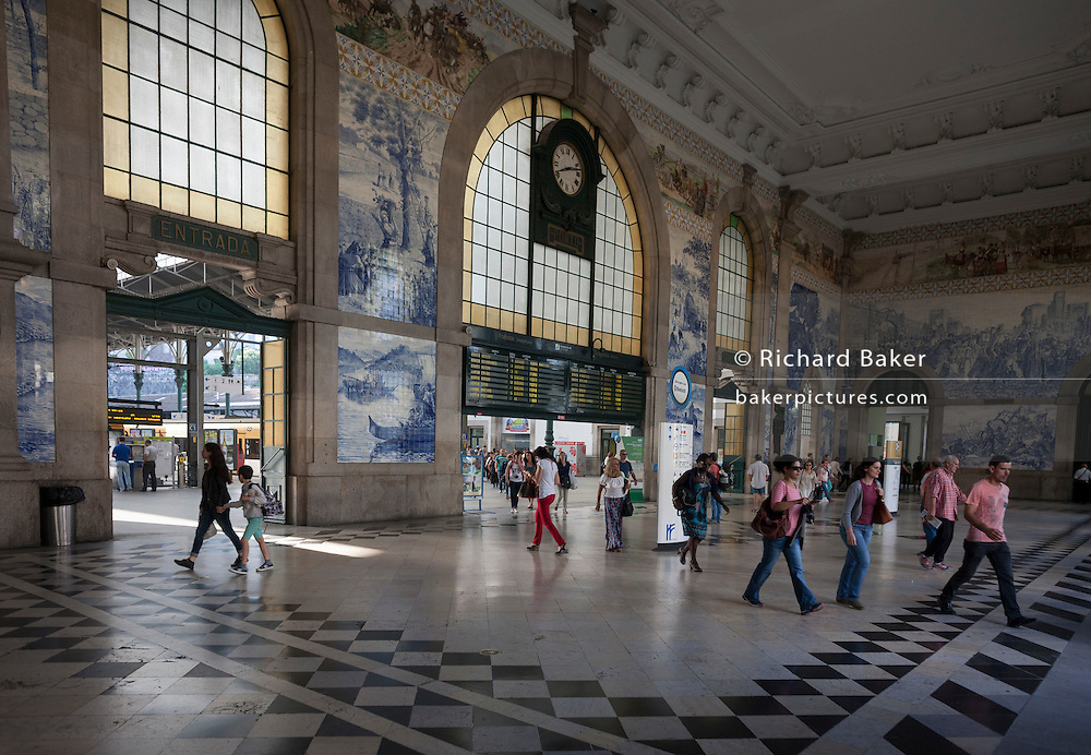 Beneath Azulejo tiles, travellers and commuters walk through the concourse of Sao Bento railway station, on 20th July, in Porto, Portugal. The name of the station derives from a Benedictine monastery built on this spot in the 16th century. The monastery fell victim of a fire in 1783, was later rebuilt, but was in a grave state of disrepair at the end of the 19th century. The most notable aspect of Sao Bento Station is the tile panels in the vestibule. There are some 20 thousand and date from 1905–1916, the work of Jorge Colaço, the most important azulejo painter of the time. The first tiles were put up on 13 August 1905. (Photo by Richard Baker / In Pictures via Getty Images)