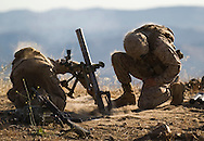 Dust is blown off of PFC Darnell, left, and his assistant gunner PFC Beat, as their 60mm mortar fires on a nearby hill during live-fire exercises for the 2nd Battalion, 5th Marine Regiment at Camp Pendleton.