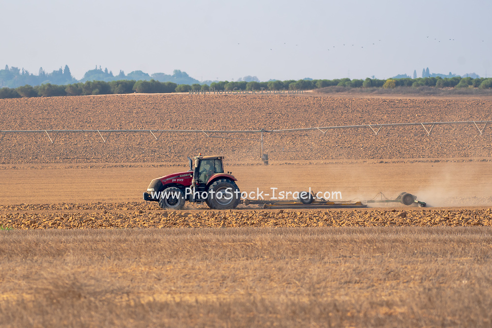 Tractor ploughing a field in the Negev Desert, Israel Photographed at Kibbutz Magen