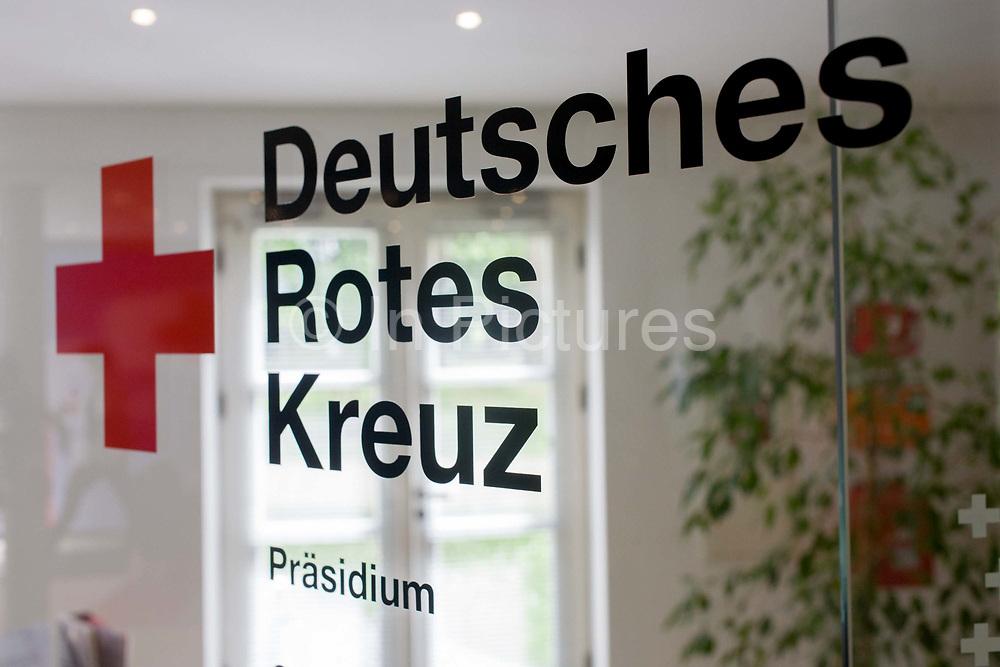 Entrance to the German Red Cross (Deutsches Rotes Kreuz - DRK) administrative HQ at 58 Carstennstrasse, Berlin. The International Red Cross and Red Crescent Movement, with its 187 National Societies, is the world's largest humanitarian network. The German Red Cross is part of this universal community, which started 150 years ago to deliver comprehensive aid to people affected by conflict, disaster, sanitary emergencies, or social hardship, guided solely by their needs. Around four million volunteers and members support the Red Cross in Germany alone. From the chapter entitled 'A life to save' and from the book 'Risk Wise: Nine Everyday Adventures' by Polly Morland (Allianz, The School of Life, Profile Books, 2015).