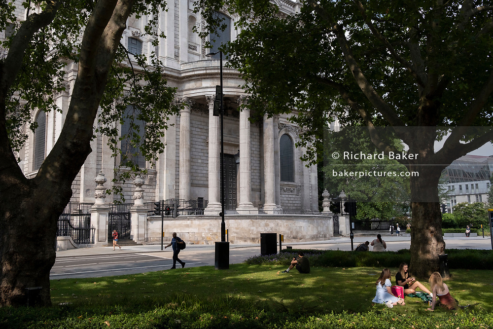 Girlfriends relax on the grass opposite the south transept of St Paul's Cathedral, on 21st July 2021, in the City of London, England.