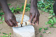 Africa, Tanzania, Lake Eyasi, Hadza men light camp fire by rubbing two sticks together.