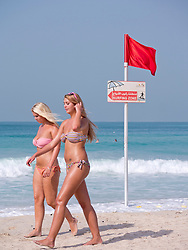 Two young western women wearing bikinis walking on public beach at Jumeirah in Dubai in United Arab Emirates