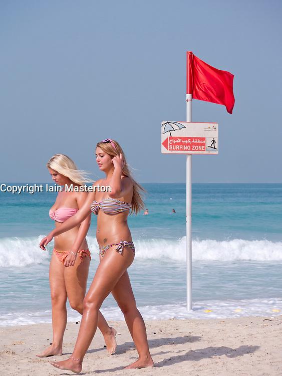 Two young western women wearing bikinis walking on public beach at Jumeirah in Dubai in United Arab Emirates