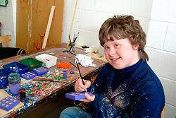 Young woman with Downs Syndrome painting a wooden pencil stand at a workshop for people with learning difficulties UK