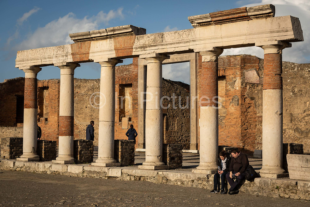 A couple sit in the sun by soe columns in the Forum at the Pompeii Archeological Park on Friday 6th March 2020 in Pompei, Italy. Park officials estimate that visitor numbers are down to a sixth of what they would normally be as a result of the spread of Coronavirus, which has prompted the closure of all Italian schools and universities, and the postponing of many sporting events. .
