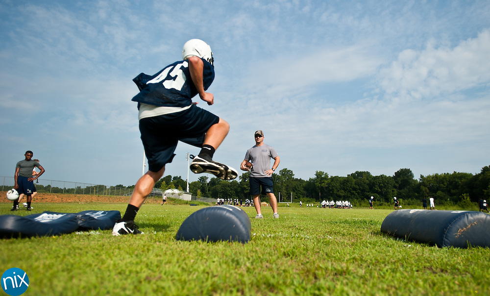 Hickory Ridge assistant coach Nate Kmieciak works with players during football practice Monday, July 30 at Hickory Ridge High School in Harrisburg. (photo by James Nix)