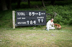 Embargoed to 0001 Monday August 28 A player sits by the scoreboard and plays with a dog during the annual friendly match between Cravens Cavaliers and Lynton & Lynmouth Cricket Club at the ground based inside the Valley of Rocks, North Devon, on Saturday August 5th, 2017.