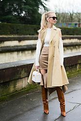 Tatiana Korsakova wears a sleeveless beige trench coat, brown boots, a bag, a white wool off shoulder top, outside Valentino, during Paris Fashion Week Womenswear Fall/Winter 2018/2019, on March 4, 2018 in Paris, France.  (Photo by Nataliya Petrova/NurPhoto/Sipa USA)