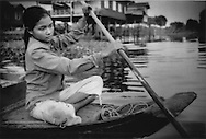 Young woman paddles the most common mode of transportation during the monsoon in the floating of Kampong Khleang, Tonle Sap, Cambodia.