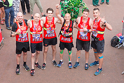 © Licensed to London News Pictures. 22/04/2018. London, UK. Firefighters from the London Fire Brigade running for Grenfell celebrate at the finish of 2018 London Marathon. Photo credit: Vickie Flores/LNP